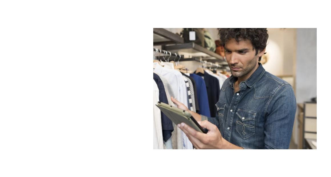 Un homme dans un rayon de vêtement, tenant et regardant une tablette tactile.